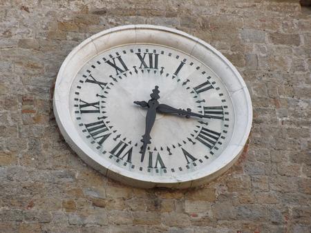 priori: The clock on the facade of the Palazzo dei Priori in Volterra village, province of Pisa . Tuscany, Italy