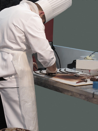 pastry chef: Pastry chef in the kitchen preparing chocolate decoration on a worktop Stock Photo