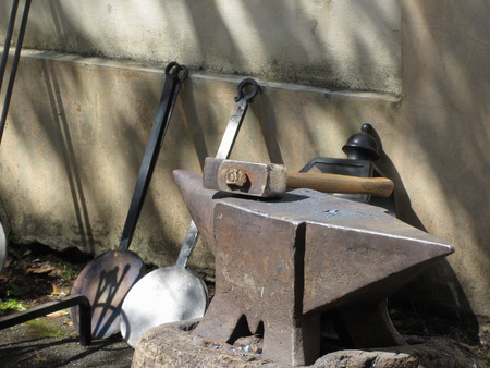 Blacksmith hammer resting on the anvil . Photo taken during outdoor public event (no ticket required) in public place . Pistoia, Italy