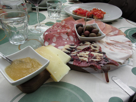 Platter of cold cuts with rustic ham prosciutto, salami, lard, cheese and olives . Tuscany, Italy