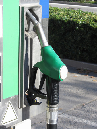 Green fuel pistol on gas station . Unleaded petrol at the pump station