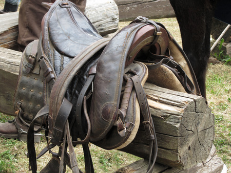 Leather saddle horse on a barrier in the stable Stock Photo - 117236958