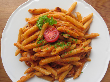 Italian penne pasta with tomato sauce, cream, mushrooms, bacon and chives . View from above