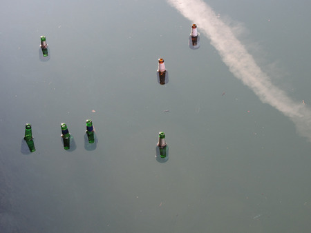 Floating bottles in still water . Pollution and litter concept