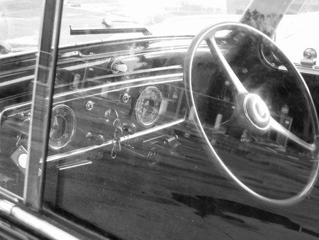 Dashboard of a classic vintage car with reflections . Nostalgia concept . Black and white photo Stock Photo