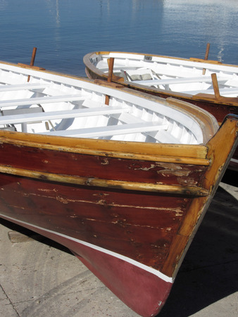 Old vintage wooden boats stand on dry dock for maintenance . Tuscany, Italy