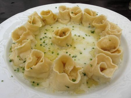 Herbs and ricotta stuffed Tortellini pasta in abundantly melted butter with chives and mountain cheese . Alto Adige, Italy Standard-Bild - 135982583