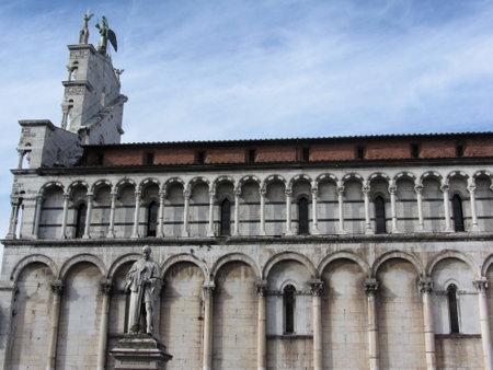 Side view of Roman Catholic basilica church of San Michele in Foro and Francesco Burlamacchi statue . Lucca, Italy