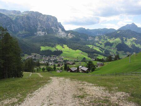 Alpine landscape with La Villa village, green pastures and firs against italian Dolomites at summer . La Villa, Bolzano, Alto Adige, South Tyrol, Italy
