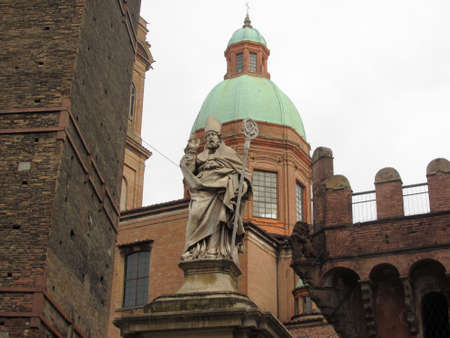 The statue of Saint Petronius (San Petronio) between the Asinelli tower and the Garisenda tower. Bologna, Italy