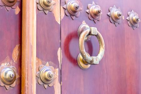 doorknocker: Golden brown colored doorknocker in a wooden door