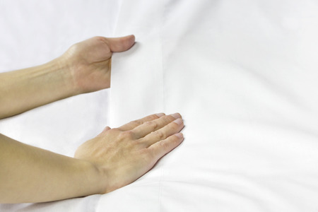 bed sheet: A pair of hands smoothing out a bed sheet. Stock Photo