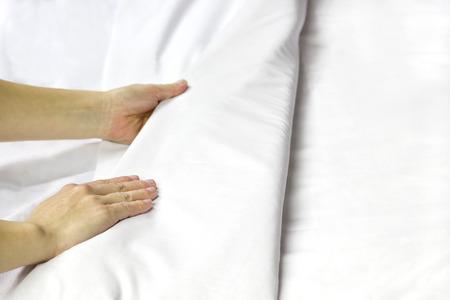A pair of hands making a bed. Foto de archivo