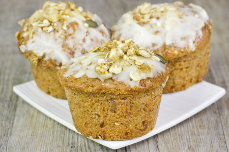 carrot cakes: Three small carrot cakes on a white plate on a wooden table.
