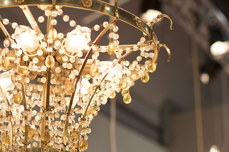 Small details from a chandelier glass lamp turn on. Foto de archivo