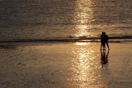 Couple silhouette on a beach shore at sunset. Foto de archivo