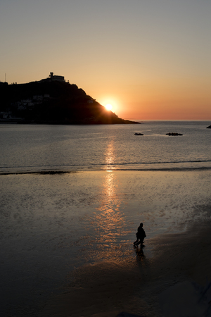 Reflection of the sun on the shore, with some people walking, in La concha beach (San Sebastian, Spain).