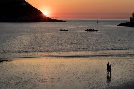 Couple walking on the shore at the beach (San Sebastian, Spain). Foto de archivo
