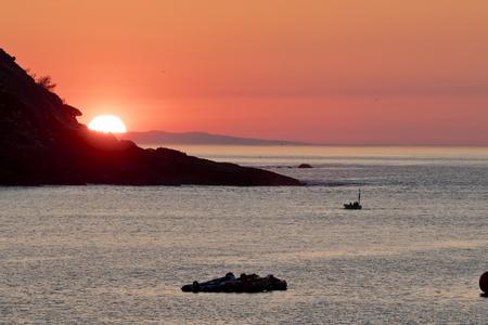 Small fishing boat returning to the port at sunset in San Sebastian (Guipuzcoa, Spain).