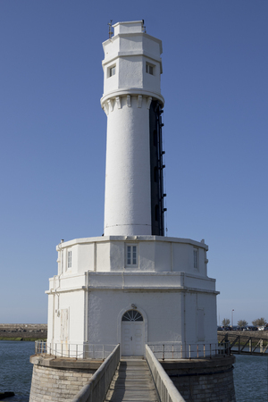 Small white lighthouse in a platform with a stone bridge access (Angle, France).