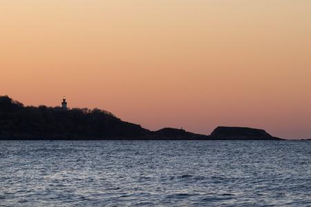 Silhouette lighthouse with light at sunset (Hendaye, France). Foto de archivo