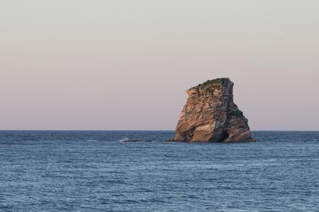 Lonely rock island at sunset (Hendaye, France).