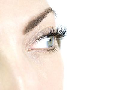 Closeup image of long black eyelashes, over a white background.