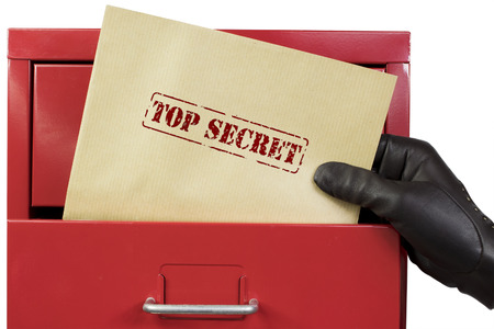 Getting top secret documents from a red file cabinet, over a white background. Foto de archivo