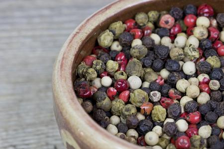 Closeup image of a bowl full of colorful peppercorns.