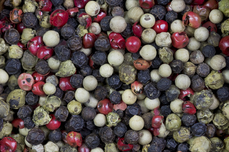 Background image of peppercorns of difference colors.