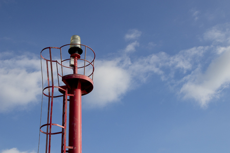 Red top navigation light over a blue sky with clouds.