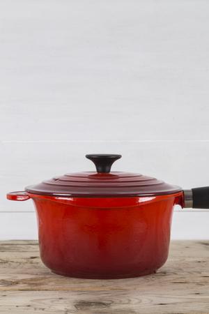 saucepan: Red saucepan with lid on table Stock Photo