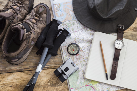 Hiking and walking equipment including hat map notebook compass binoculars poles and boots