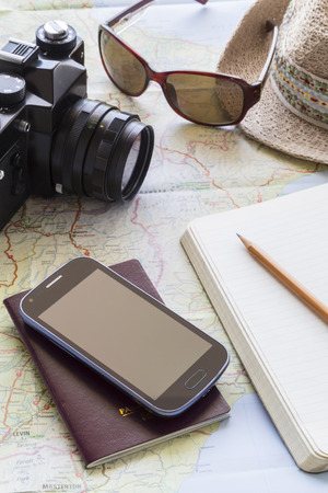 voyage: Travel items including camera sunglasses hat smartphone passport and journal placed on an open map on a tabletop Stock Photo