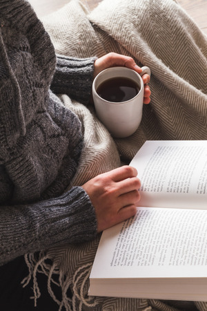 Woman wearing gray woolly cardigan enjoying a mug of tea and reading a book under a cozy blanket, hygge concept Stockfoto