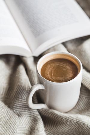 Cozy cup of hot chocolate with book, hygge concept