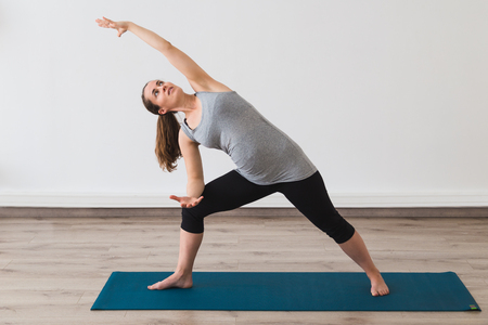 Young pregnant woman doing extended side angle yoga posture Stock Photo