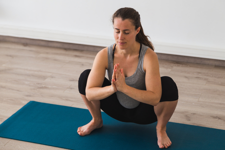 Young pregnant woman doing prenatal yoga posture with namaste hands