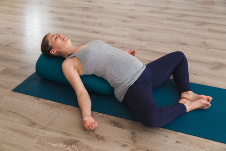 Young woman lying on yoga mat using bolster cushion