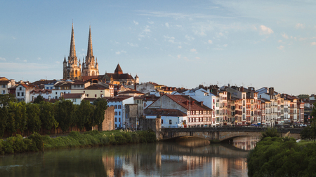 Cityscape view of Bayonne, France, in the south western basque country region, looking along the river Nive witha bridge in the foreground and the old townhouses and spires of the cathedral behind it.