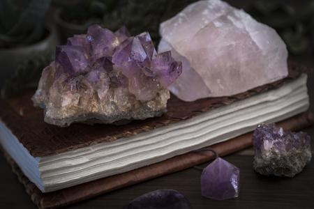 Quaderno o diario chiuso rilegato in pelle con cristalli di ametista e quarzo rosa posizionati sopra e intorno