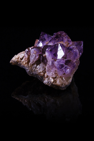 Large chunk of rough amethyst crystal on reflective black surface Stock Photo