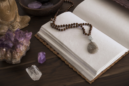Open leatherbound writing journal or notebook surrounded by crystals on a wooden surface