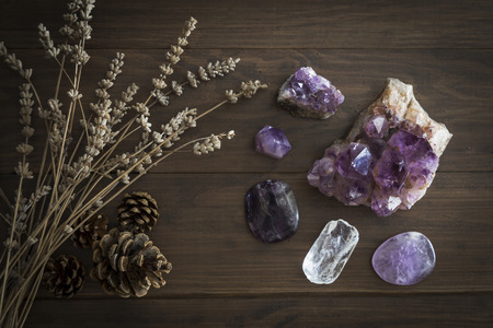 Selection of amethyst quartz and purple fluorite with dried lavender and pine cones on wooden surface