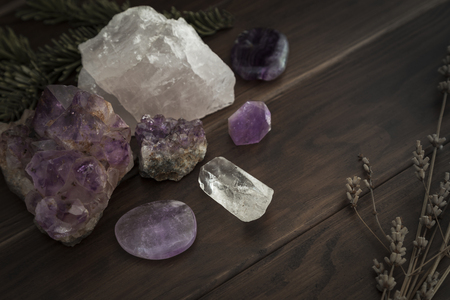 Selection of crystals and stones placed on wooden surface with foliage Archivio Fotografico