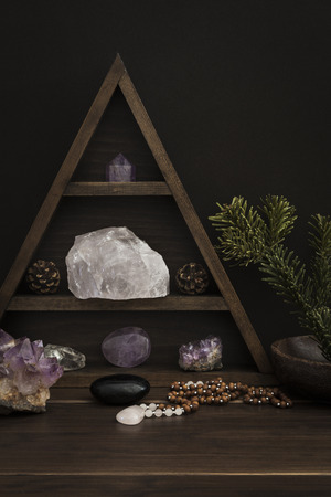 Triangular crystal shelf on wooden surface with jewellery stones and foliage