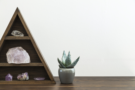 Triangular wooden crystal shelf on wooden surface with potted succulent plant
