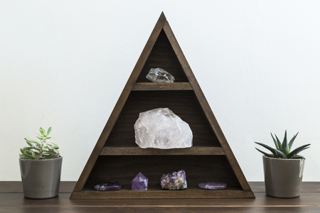 Triangular wooden crystal shelf with succulent plants either side on wooden surface