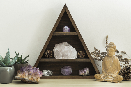 Triangular wooden crystal shelf with green succulent plants foliage and wooden statue of Buddha Foto de archivo