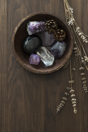 Wooden bowl with crystal and stone collection next to dried lavender on table